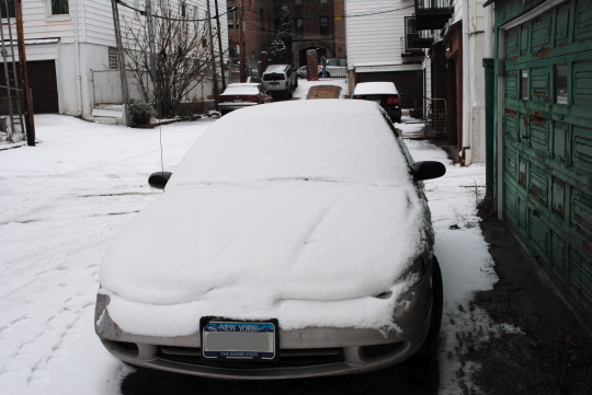 [nearby car covered by snow]